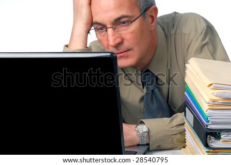 Businessman working at his computer with some files on a side
