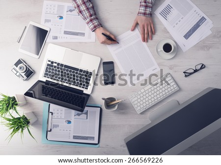 Businessman working at office desk and signing a document, computers and paperwork all around, top view #266569226