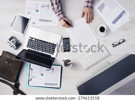 Businessman working at office desk and signing a document, computers and paperwork all around, top view