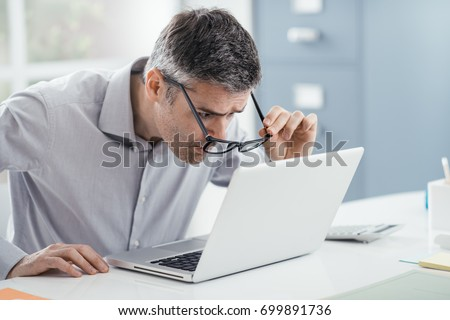 Businessman working at office desk, he is staring at the laptop screen close up and holding his glasses, workplace vision problems - Shutterstock ID 699891736
