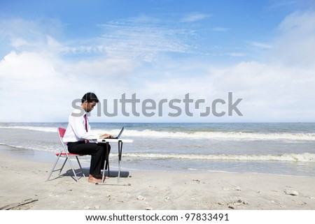 Businessman working at the beach with laptop computer