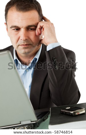 Businessman working behind laptop, looking at his cell phone thinking