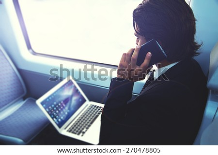 Businessman working busy with laptop on the way to work while sitting in train next to the window, handsome male having cell phone conversation, business man commuting to work while using technology