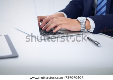 Businessman working by typing on laptop computer. Man's hands on notebook or business person at workplace. Employment  or start-up concept #739090609