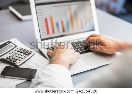 Businessman working in his laptop in a modern office.