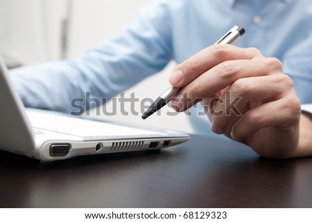Businessman working in his office holding a pen