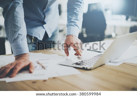Businessman working in modern cretive studio. Using generic design laptop. Architectural project on table. Blurred background, horizontal mockup.