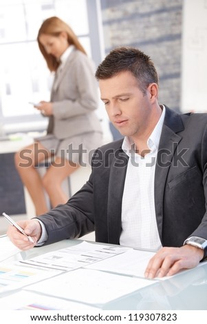 Businessman working in office sitting at desk, woman texting in background