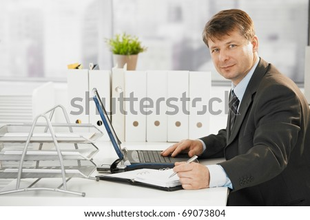 Businessman working in office, using laptop computer. Looking at camera.