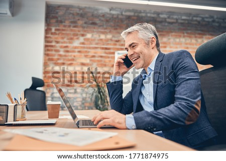 Businessman working in office with computer and talking on phone in the loft office