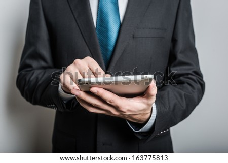 Businessman working on a digital tablet against gray background