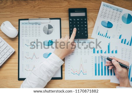 Businessman working on a graph document financial report and analysis calculation cost with calculator at office desk and other objects around, Top view workspace.