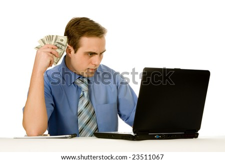 Businessman working on a laptop holding money. Isolated on white.
