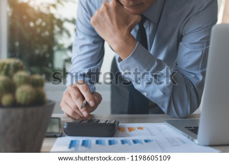 Businessman working on calculator to calculate and scrutiny review accounting data, business income, summary report and marketing plan in office with laptop computer on desk, business analysis concept