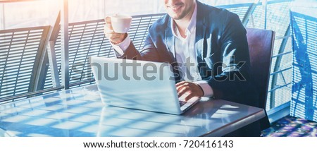 businessman working on computer, drinking coffee and smiling, abstract business banner background with place for text #720416143
