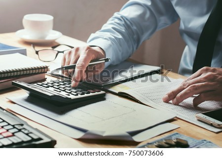 businessman working on desk office with using a calculator to calculate the numbers, finance accounting concept #750073606