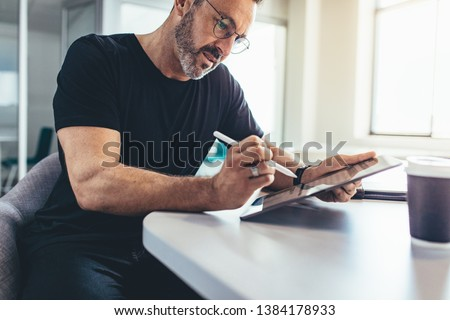 Businessman working on digital tablet marking few imports points with a stylus. Male entrepreneur checking emails on his tablet computer. Stock fotó ©
