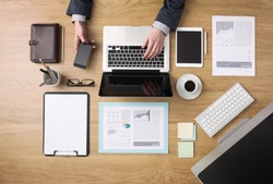 Businessman working on his laptop and using a mobile phone with paperwork and financial reports around, desktop top view
