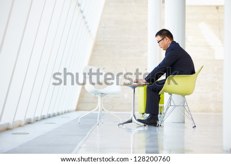 Businessman Working On Laptop At Table In Modern Office