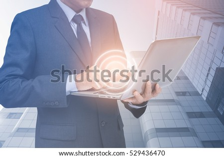 Businessman working on laptop computer and sparkle  wifi icon with modern office buildings in low angle view background, online business internet of things IOT concept
