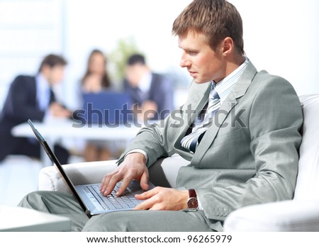 Businessman working on laptop computer at office lobby - stock photo
