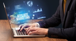 Businessman working on laptop with AFFILIATE MARKETING inscription, new business concept