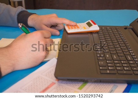 Businessman working on office desk with Calculator, a computer, a pen and document. Man, counting money and making calculations