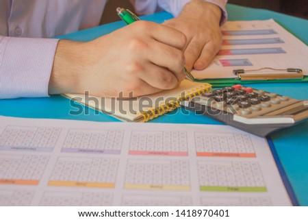 Businessman working on office desk with Calculator, a pen and document. Man, counting numbers and making calculations