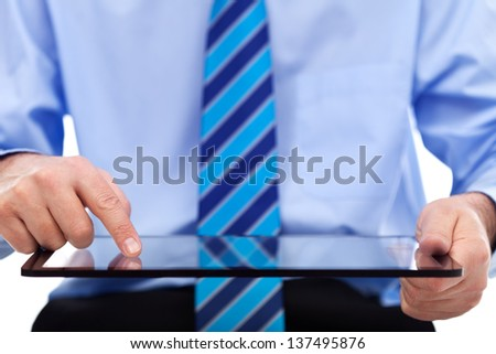 Businessman working on tablet computer - closeup on device and hands, copyspace