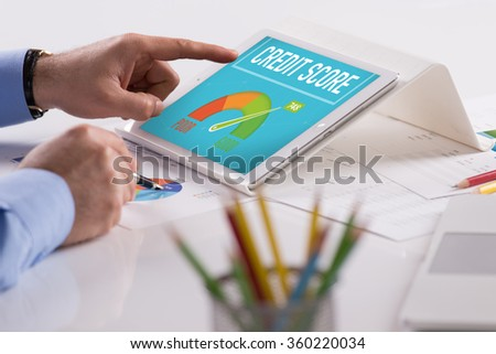 Businessman working on tablet with CREDIT SCORE on a screen