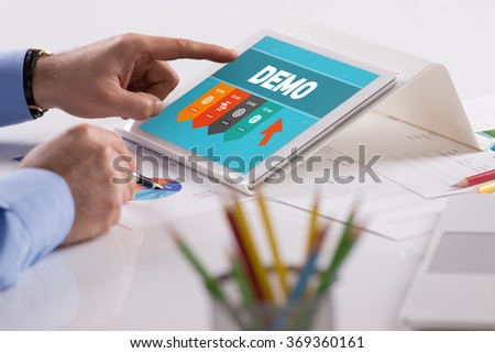 Businessman working on tablet with DEMO on a screen