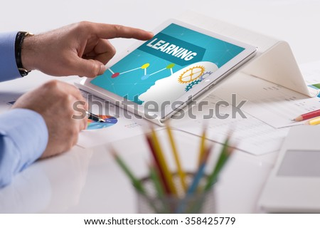 Businessman working on tablet with LEARNING on a screen