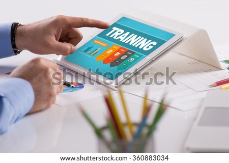 Businessman working on tablet with TRAINING on a screen