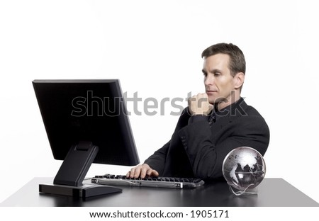 Businessman working on the computer with an earth globe on his desk.