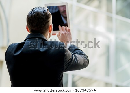 Businessman working on the tablet. Young man in formal wear rear view.