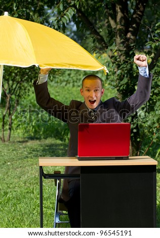 Businessman working outdoors, hiding from the sun under umbrella