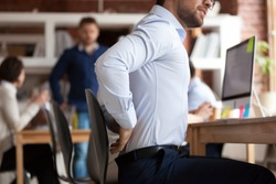 Businessman working sitting at desk feels unhealthy suffers from lower back pain. Damage of intervertebral discs, spinal joints, compression of nerve roots caused by wrong posture and sedentary work