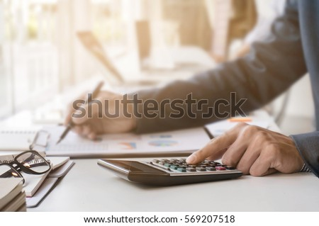 Businessman working with calculator and document data