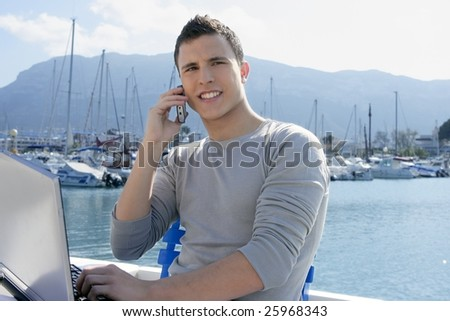 Businessman working with computer on a boat, nice outdoor office