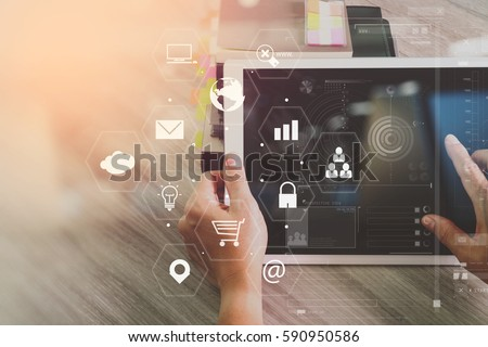businessman working with digital tablet and book and document on wooden desk in modern office with virtual icons interface