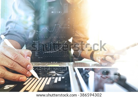 businessman working with digital tablet computer and smart phone with financial business strategy layer effect on wooden desk as concept