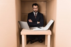 businessman working with documents and cardboard laptop in box