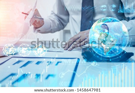 Businessman working with documents in office with double exposure of business infographics interface. Stock market and future concept. Toned image. Elements of this image furnished by NASA #1458647981