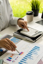 Businessman working with graph papers and laptop calculator to calculate company financial results. On a wooden table in offices and businesses, tax, accounting, statistics and vertical analytical res