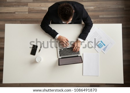 Businessman working with laptop and documents sitting at office desk, employee or company ceo using online apps software at workplace, man in suit typing on computer, top overhead view from above #1086491870