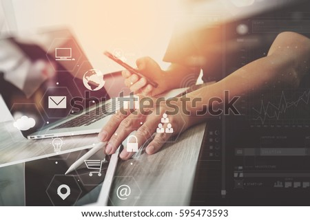 businessman working with laptop computer and digital tablet and smart phone and book and document on wooden desk in modern office with virtual icons interface