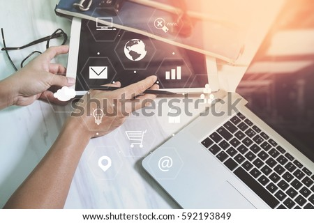 businessman working with laptop computer and digital tablet and suitcase on wooden desk in modern office with virtual icons interface