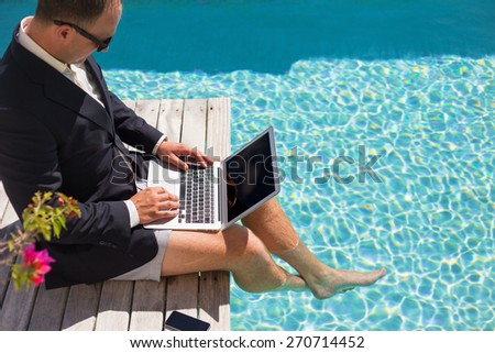 Businessman working with laptop computer by the pool