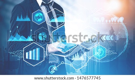 Businessman working with laptop in modern city with double exposure of business infographics interface. Concept of market analysis and big data. Toned image #1476577745