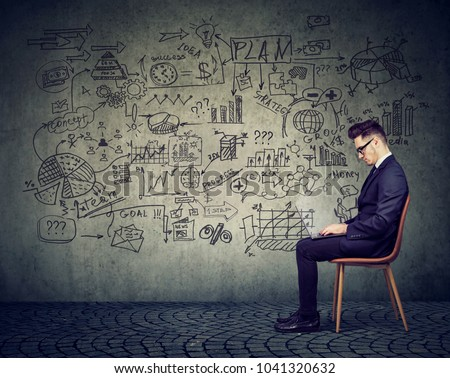 Businessman working with laptop on a business plan on the wall background full of economy drawings #1041320632